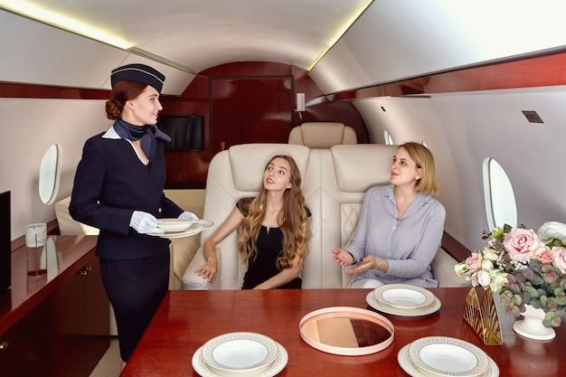 A aeromoça está atendendo passageiros do sexo feminino em um jato particular.