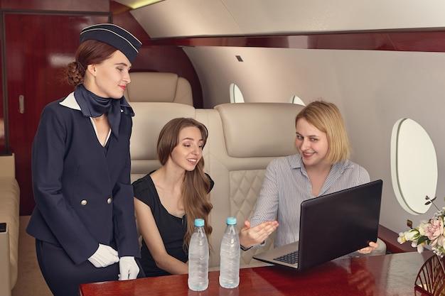 A aeromoça está olhando para a tela do laptop, que a passageira está mostrando no jato executivo.