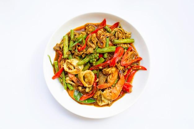 A agitação picante fritou o shimp, o calamar e a carne de porco com pasta do sul tailandesa do pimentão e longbean no fundo branco.