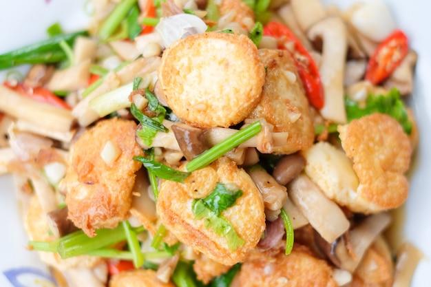 A agitação quente fritou o tofu e a carne de porco e o cogumelo com molho de feijão preto servem no prato branco ajustado na tabela marrom - conceito caseiro do alimento.
