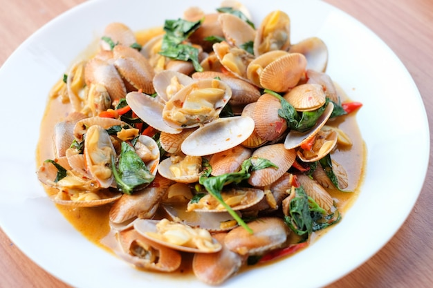A agitação quente moluscos fritados com pasta e manjericão roasted do pimentão serve no prato branco ajustado na tabela marrom - conceito caseiro do alimento.