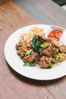 A agitação tailandesa do estilo fritou a galinha das coxas com sal e pimentão. servido com molho de pimenta.