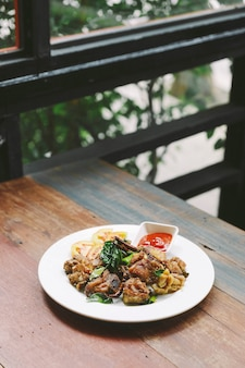 A agitação tailandesa do estilo fritou a galinha das coxas com sal e pimentão.