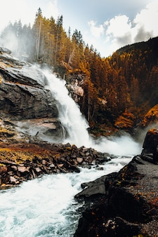 A água cai em uma montanha rochosa marrom durante o dia