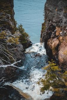 A água cai na costa rochosa durante o dia
