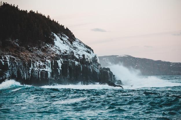A água cai na montanha rochosa