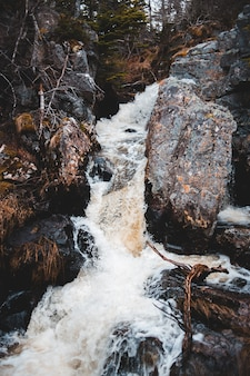 A água cai no meio da montanha rochosa