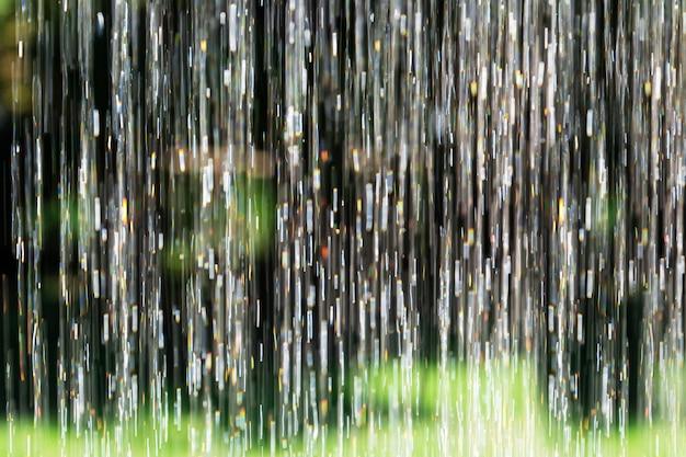 A água de derramamento borrada do fundo verticalmente com sol reflexivo destaca no jardim.