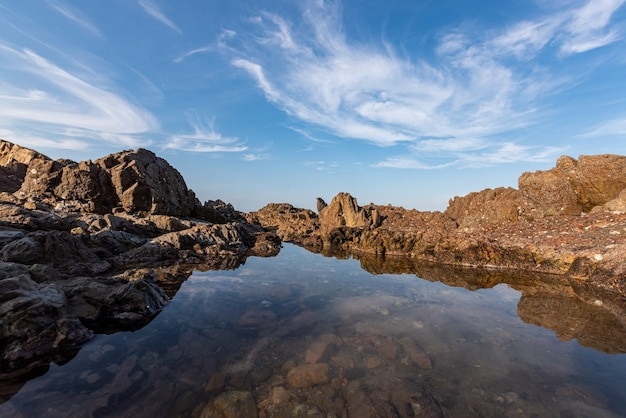 A água do mar entre os recifes à beira-mar reflete os recifes amarelos e o céu azul