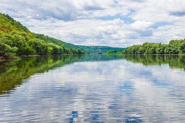 A água do rio dniester em close-up com florestas nas laterais feitas de um barco.