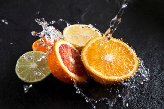 A água é derramada em metades de frutas cítricas frescas em um fundo de pedra escura