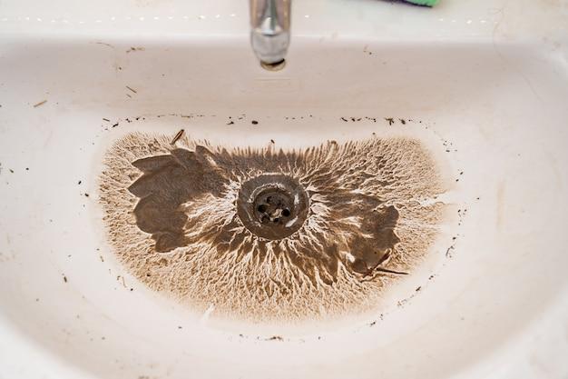 A água é drenada para o ralo sujo da pia após o bloqueio ser removido