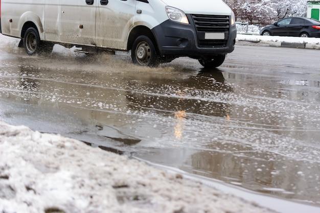 A água espirra sob as rodas de um veículo que se move através de poças sujas de neve derretida da primavera. águas da inundação após uma nevasca.