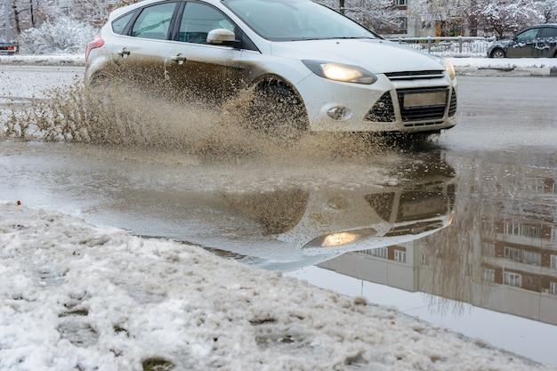 A água espirra sob as rodas de um veículo que se move através de poças sujas de neve derretida da primavera. águas da inundação.