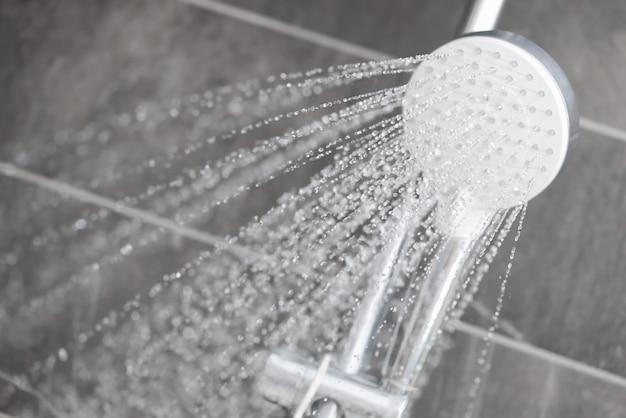 A água flui da chuva em gotas para o banheiro do hotel