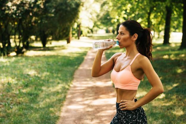 A água potável da mulher do atleta do ftness após dá certo exercitando ao ar livre.