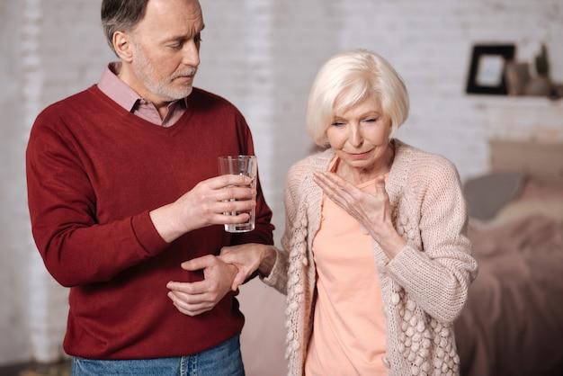 A água vai ajudar. senhora idosa, sentindo-se muito mal e o marido propondo-lhe um pouco de água.
