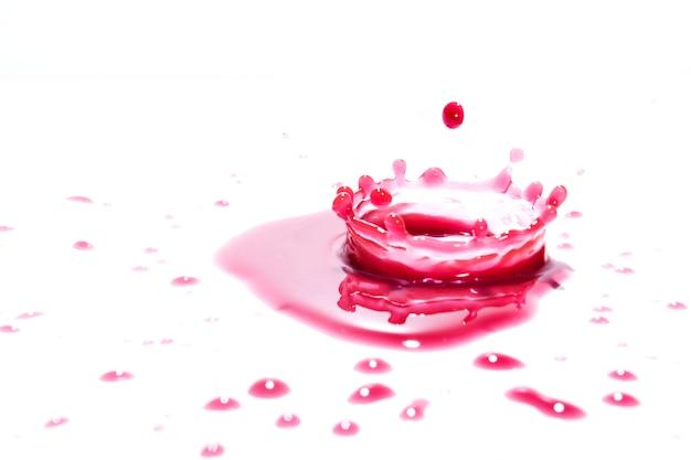 A água vermelha espirra em um fundo branco, fotografia. salpicos de água vermelha.