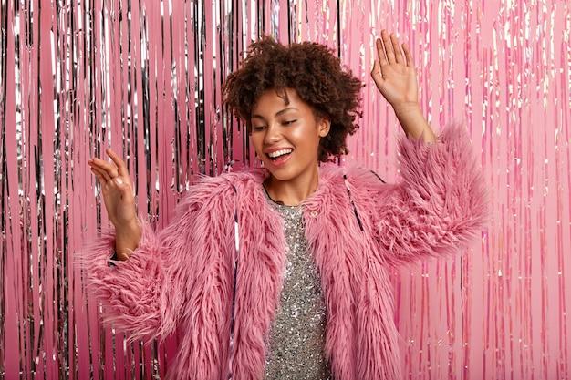 A alegre mulher afro-americana ri sinceramente, sente-se relaxada, dança enquanto ouve música favorita, usa casaco de pele rosa e vestido cintilante, modelos sobre parede rosada. celebração