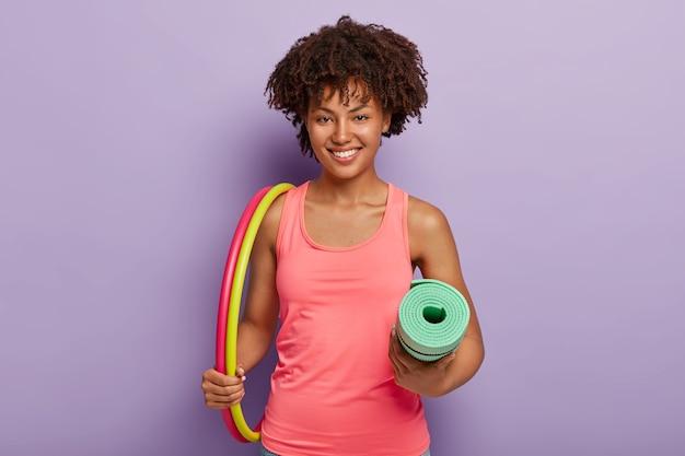 A alegre senhora afro-americana carrega dois bambolês, karemat enrolado e exercícios para perder peso