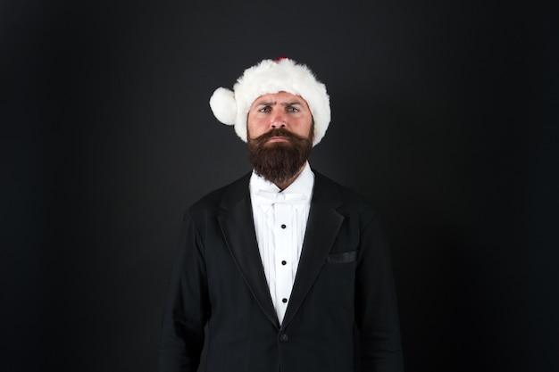 A alta temporada é dezembro. homem de negócios sério do papai noel. empresário comemora o natal e o ano novo. empresário vestido para a festa do escritório. empresário usa chapéu de papai noel com trajes formais.