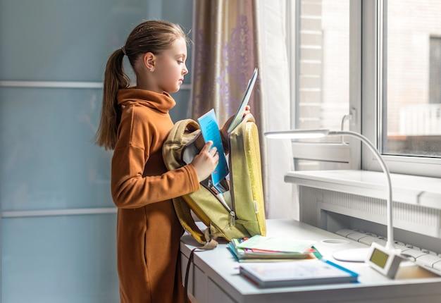 A aluna em casa vai para a escola. criança recolhe uma mochila. de volta à escola. preparação para a escola.