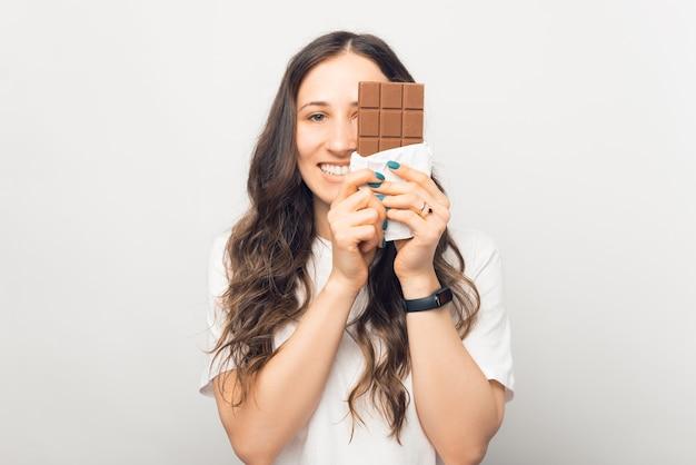 A amante de chocolate está cobrindo metade do rosto.