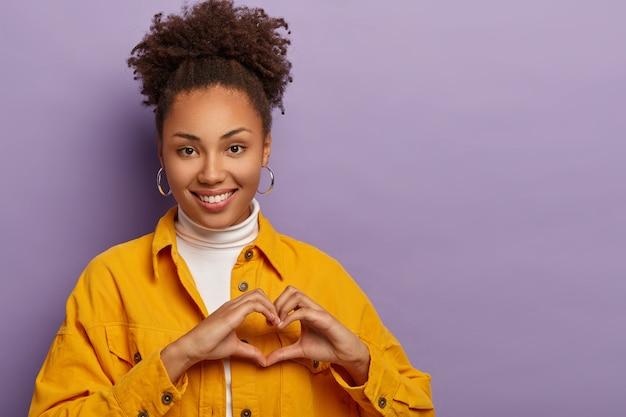 A amável mulher afro-americana faz gestos de coração, confessa que está apaixonada, expressa simpatia e alegria, tem sentimentos sinceros, usa roupas elegantes, isoladas sobre fundo roxo.