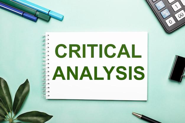 A análise crítica é escrita em uma folha branca sobre um fundo azul perto do papel de carta e da folha de scheffler