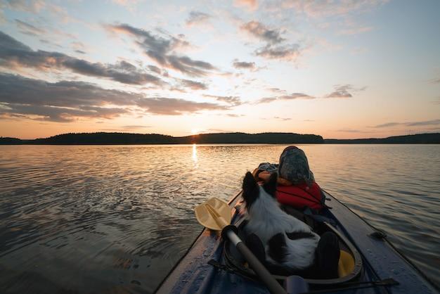 A anfitriã e o cachorro estão navegando no lago em um barco de caiaque ao pôr do sol
