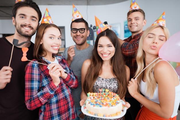 A aniversariante está segurando um bolo com velas.