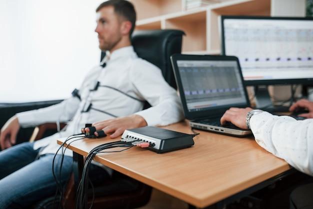 A ansiedade mostra que você não é tão honesto. homem suspeito passa no detector de mentiras no escritório. fazendo perguntas. teste de polígrafo