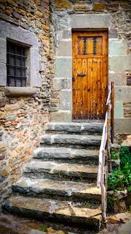 A antiga porta de madeira e escadaria de pedra
