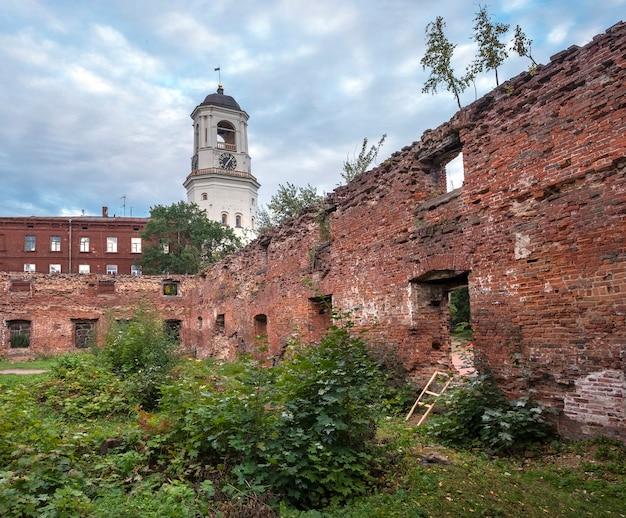 A antiga torre do relógio na cidade de vyborg rússia através das ruínas de um templo