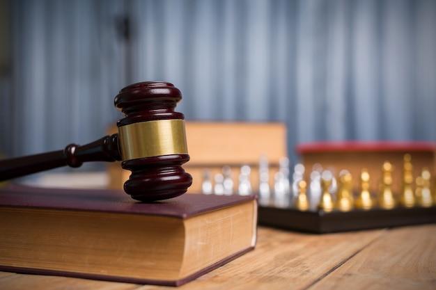 A antiguidade do gavel do juiz resistiu à xadrez de madeira, dourada do vintage e aos livros de lei no tribunal.