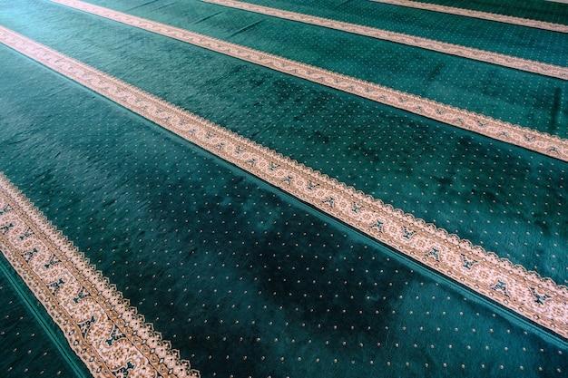 A aparência tapete de oração verde na mesquita. padrão de linhas principais