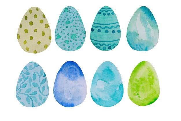 A aquarela, os ovos da páscoa azuis e verdes tirados mão ajustou a ilustração do cartão, isolada no branco.