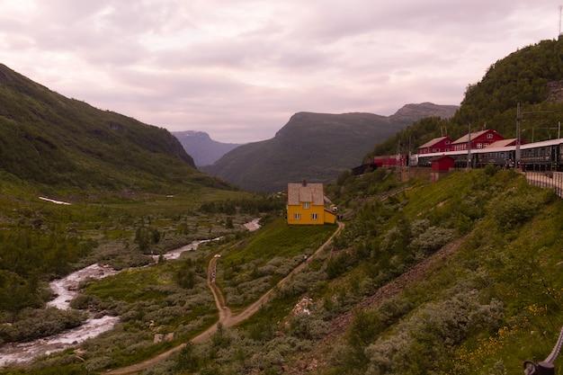 A área de flåm e seu trem turístico jogam as montanhas norueguesas, na noruega.
