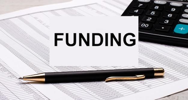 A área de trabalho contém relatórios, uma calculadora, uma caneta e um cartão branco com o texto financiamento. conceito de negócios.