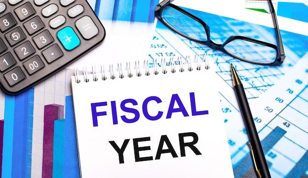 A área de trabalho contém tabelas coloridas, calculadora, óculos, caneta e caderno com o texto ano fiscal