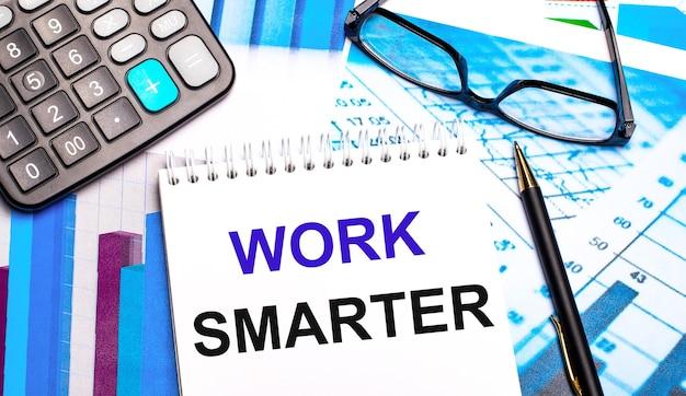 A área de trabalho contém tabelas coloridas, uma calculadora, óculos, uma caneta e um caderno com o texto trabalhe mais inteligente