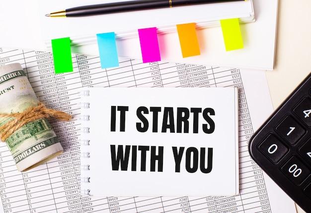 A área de trabalho possui relatórios, blocos de notas, calculadora, caneta, dinheiro e bloco de notas com adesivos coloridos e o texto começa com você