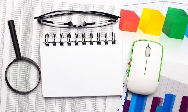 A área de trabalho tem uma lente de aumento, um mouse de computador, gráficos coloridos, óculos e um caderno em branco para colar texto ou ilustrações. conceito de negócios