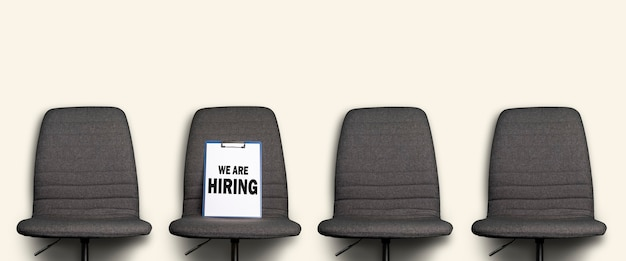 A área de transferência com a inscrição que estamos contratando encontra-se em uma cadeira de escritório cinza em um branco.