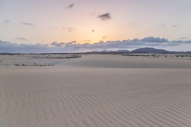 A areia, as dunas e as montanhas vulcânicas no por do sol ajardinam no parque natural de corralejo, fuerteventura, ilhas canárias, espanha.
