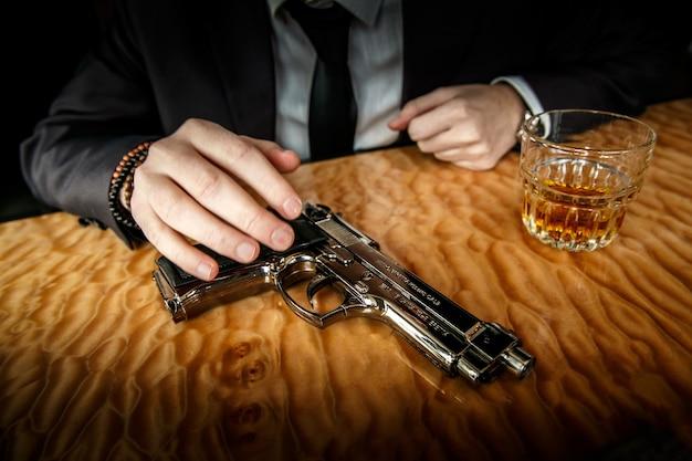 A arma com vidro e conhaque na mesa de mármore