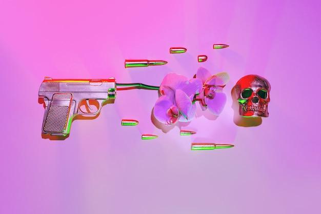 A arma dourada atira uma flor de orquídea, ao lado de balas voadoras em um fundo rosa, o conceito contra a guerra.
