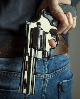 A arma em mãos.