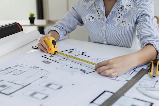 A arquiteta está usando uma fita métrica para medir as plantas da casa. ela está verificando as plantas da casa que ela projetou antes de enviá-las aos clientes. ela projeta a casa e o interior.
