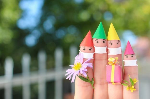 A arte do dedo da família com máscaras médicas comemorando um aniversário